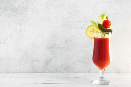 Bloody Mary Cocktail in glass with garnishes. Tomato Bloody Mary or Caesar spicy drink on white background with copy space.