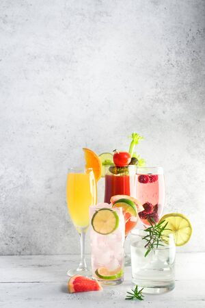Brunch or Breakfast Cocktails Assortment. Bloody Mary, Mimosa drink and various citrus alcohol refreshing cocktails on light table, copy space.