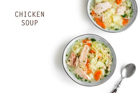 Chicken soup with noodles and vegetables in bowl isolated on white background, top view, copy space. Homemade healthy meal - fresh chicken or turkey soup.