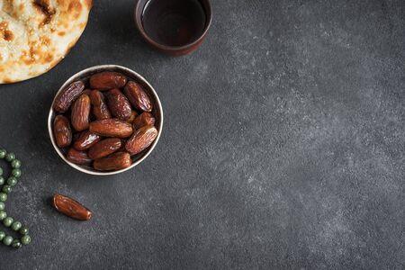 Traditional Ramadan, iftar meal - date fruits, ramadan fresh bread and water on black table, top view, copy space. Ramadan Kareem concept.