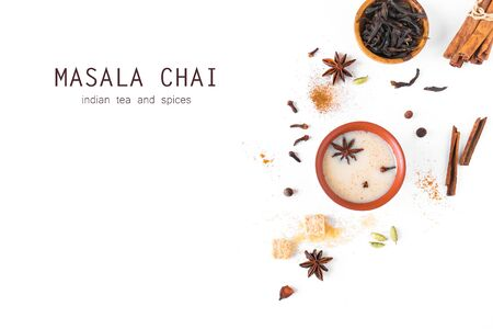 Masala Chai Tea in ceramic cup with ingredients. Traditional indian spicy black tea with milk isolated on white background, top view, copy space.