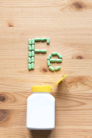 Green pills forming shape to Fe alphabet on wooden Stok Fotoğraf