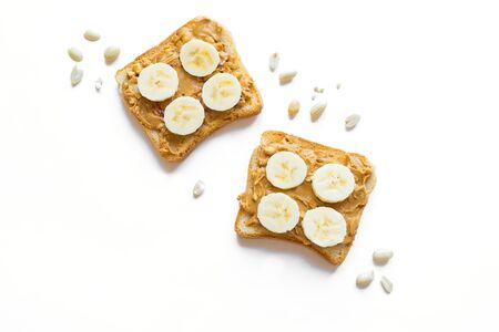 Slice of toast bread with peanut butter and banana isolated on white, top view, copy space. Sweet sandwich, unhealthy food.