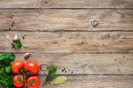 Herbs and spices with fresh tomatoes on wooden background. Cooking and healthy eating concept, top view, copy spce.