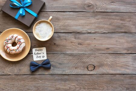 Happy Fathers Day flat lay on wooden desk, copy space. Morning coffee, donut, gift box with greeting card. Father's Day celebration concept.