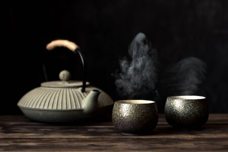 Teapot and tea cups with steaming fresh tea. Traditional japanese chinese iron teapot and ceramic teacups, asian tea set on dark background, copy space. Zdjęcie Seryjne