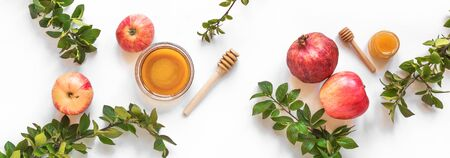 Rosh Hashanah jewish New Year holiday concept. Creative layout of traditional symbols - apples, honey, pomegranate isolated on white, top view, banner. Imagens
