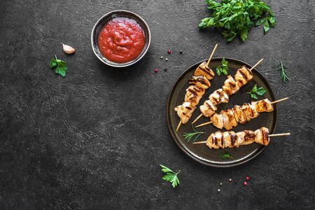 Chicken skewers or kebabs on black table, top view, copy space. Grilled meat pork, chicken or turkey shish kebab with tomato sauce, herbs and spices, barbeque meal.