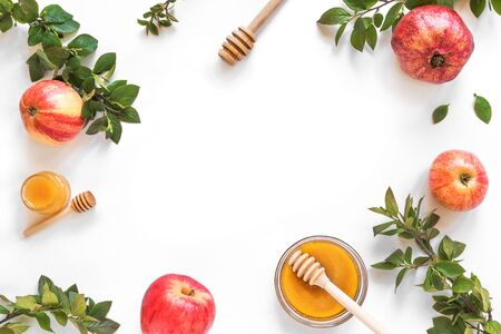 Rosh Hashanah jewish New Year holiday concept. Creative layout of traditional symbols - apples, honey, pomegranate isolated on white, top view, copy space.