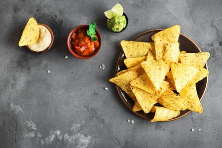 Mexican Corn Chips Nachos and set of traditional dips, top view, copy space. Tortilla or Nacho Chips with sauces for snack.