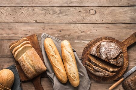 Fresh Bread on wooden background, top view, copy space. Homemade fresh baked various loafs of wheat and rye bread flat lay.