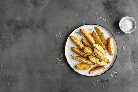 Roasted potato wedges with herbs and sea salt on plate, top view, copy space. Homemade oven baked potato snacks and sour cream sauce.