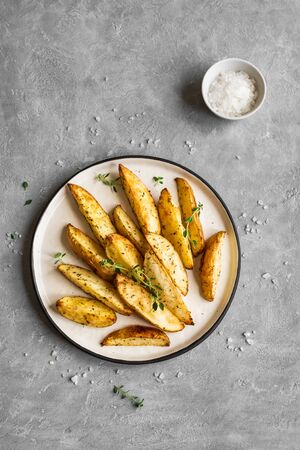 Roasted potato wedges with herbs and sea salt on plate, top view, copy space. Homemade oven baked potato snacks and sour cream sauce. Reklamní fotografie