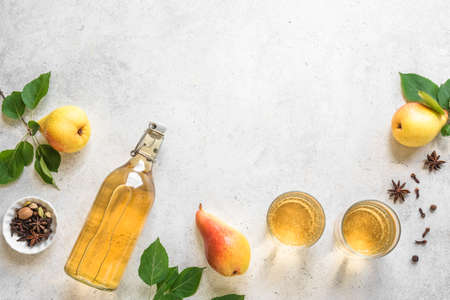 Pear cider drink or fermented fruit drink  in glasses and bottle and organic pears on white, top view, copy space. Healthy homemade hard pear cider with spices. Stock Photo