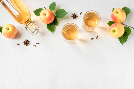 Apple cider drink or fermented fruit drink and organic apples on white, top view, copy space. Healthy homemade apple cider recipe with spices.