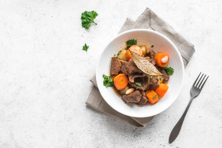 Beef meat stewed with potatoes, carrots and spices on white background, top view. Homemade winter comfort food - slow cooked meat stew in bowl.
