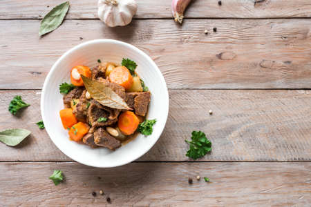 Beef meat stewed with potatoes, carrots and spices on wooden background, top view, copy space. Homemade winter comfort food - slow cooked meat stew in bowl.