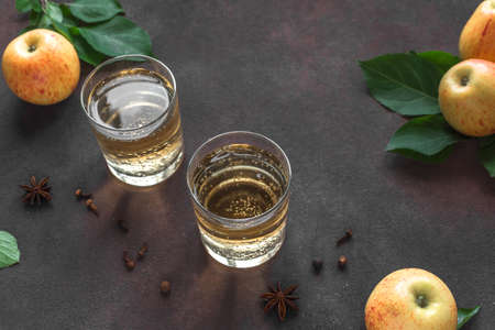 Apple cider drink or fermented fruit drink and organic apples in glasses close up. Healthy homemade apple cider recipe with spices.