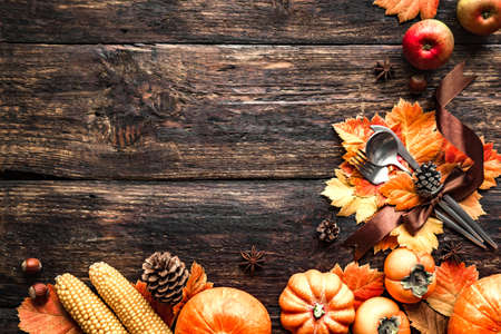 Autumn Thanksgiving Table Setting. Cutlery and autumn leaves on wooden table with pumpkins and autumn decor, Thanksgiving holiday menu concept.