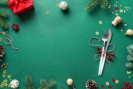 Christmas Table Setting with fir branch and ornaments on green, flat lay, copy space. Christmas dinner, party design, concept - table setting with festive decoration.