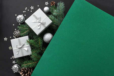 Christmas composition. Christmas decor, gift boxes, pine branches on multilayer green and black background. Top view, copy space. Reklamní fotografie