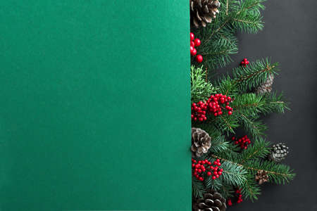 Christmas composition. Christmas tree branches and cones on multilayer green and black background. Top view, copy space.
