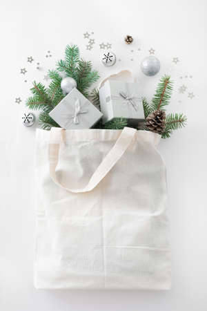 Christmas composition. Eco bag with Christmas decor, gift boxes, pine branches on white background. Christmas coming and gift delivery concept. Top view, copy space. Imagens