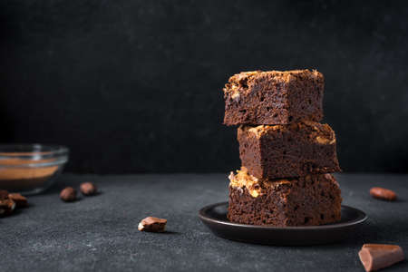 Stack of brownies on black background. Delicious homemade chocolate dessert, brownie with peanut butter, copy space.