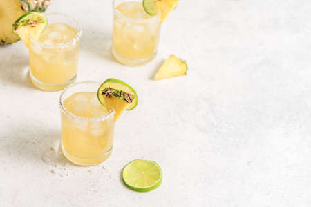 Pineapple Margarita Cocktail. Summer boozy refreshing drink with tequila, pineapple in glasses with salt rim, copy space.