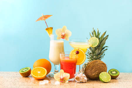 Summer tropical cocktail drinks, fruits and flowers, blue background, copy space. Summer vacation and beach relax concept. Set of three cocktails.