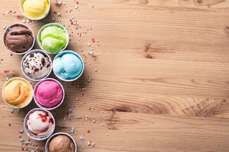 Ice Cream Assortment. Various ice creams or italian gelato on wooden background, top view, copy space. Frozen yogurt in small cups - healthy summer dessert. 免版税图像