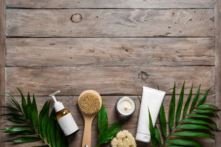 Natural skin care products, massage brush and green leaves on wooden, top view, copy space. Natural eco beauty and organic skin care concept. 免版税图像