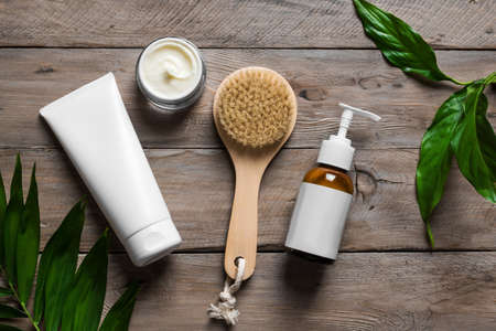 Natural skin care products, massage brush and green leaves on wooden table. Natural eco beauty and organic skin care concept. 免版税图像