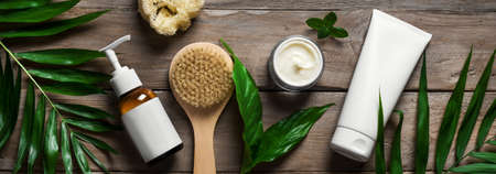 Natural skin care products, massage brush and green leaves on wooden, banner. Natural eco beauty and organic skin care concept.