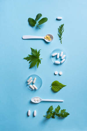 Homeopathy, naturopathy and alternative herbal medicine. Capsules and pills, green plant leaves on blue background, top view, pattern.