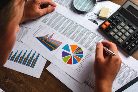 statistician: Analyzing financial data and counting on calculator. Stock Photo