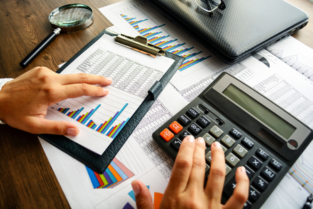 Analyzing financial data and counting on calculator. Stock Photo