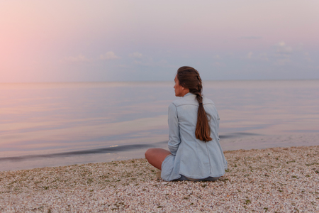 Young beautiful lonely girl is sitting on the beach and looking into the distance of the sea at sunset (dawn).