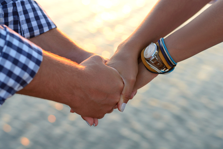 Two lovers (guy and girl) hold hands tightly on the beach.
