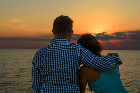 Two lovers (pair) in an embrace sit on the seashore and look at the sunset. Romance and Travel Stock Photo