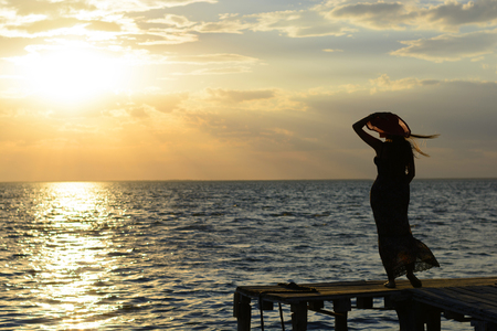 Young young lonely girl sits on the seashore and looks into the distance of the ocean Stock Photo
