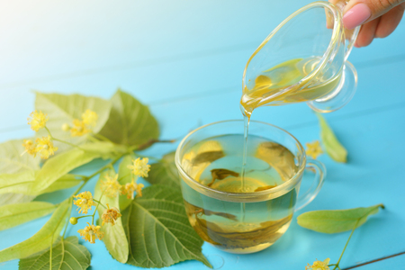 Green medicinal lime tea, linden flowers and honey on a wooden background. Treated tea.