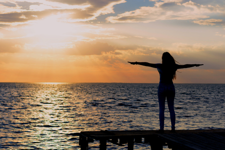 A young slender girl standing on a wooden bridge (fishing bridge) spreading her hands over the sea and looking at the sunset (dawn) of the sun. Life and freedom.