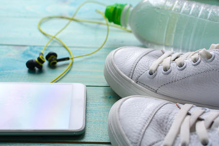 Sports accessories - krassovki (sneakers), a bottle of water, a phone with headphones. Health and sport.