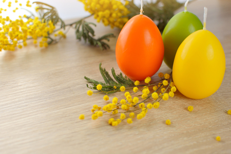 Candles in the shape of eggs and mimzy branches on a wooden light background. Holiday - Easter. Religion and rest.