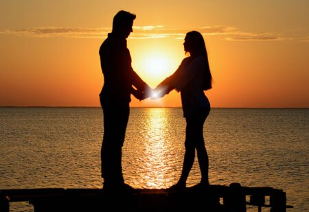 Two lovers (a boy and a girl) holding hands while standing on a wooden bridge near the ocean at sunset