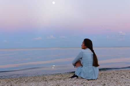 A young lonely and sad woman sits by the ocean (sea) and looks into the distance. Thoughts and concentration.
