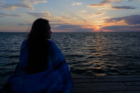 A young lonely and sad woman sits on a wooden bridge near the ocean (sea) and looks at the sunset. Thoughts and concentration.