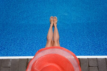 Beautiful, young girl in a hat sunbathes by the pool. Rest, tourism, holidays Stock Photo