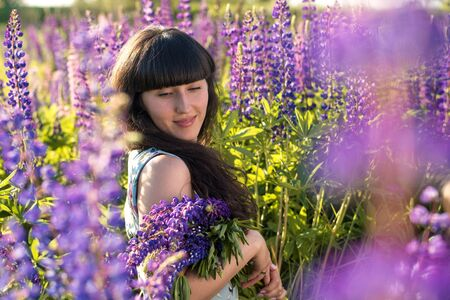 A young beautiful girl with a flowering meadow (field). Joy, romance, date, love.